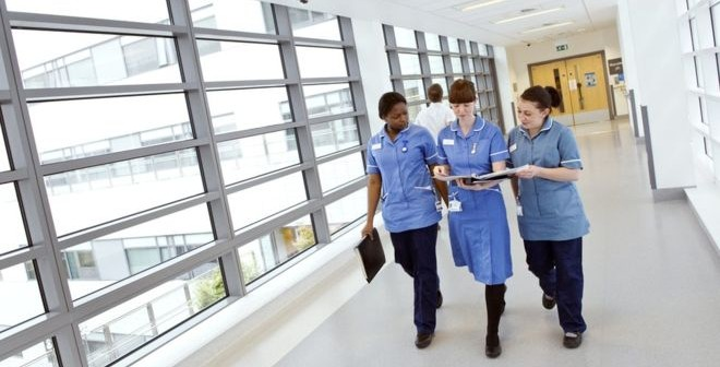 _88461316_c0151526-nurses_walking_along_hospital_corridor-spl